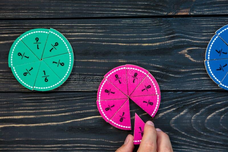 As crianças entregam movem frações coloridas da matemática no fundo ou na tabela de madeira escura Matemática engraçada criativa  foto de stock royalty free