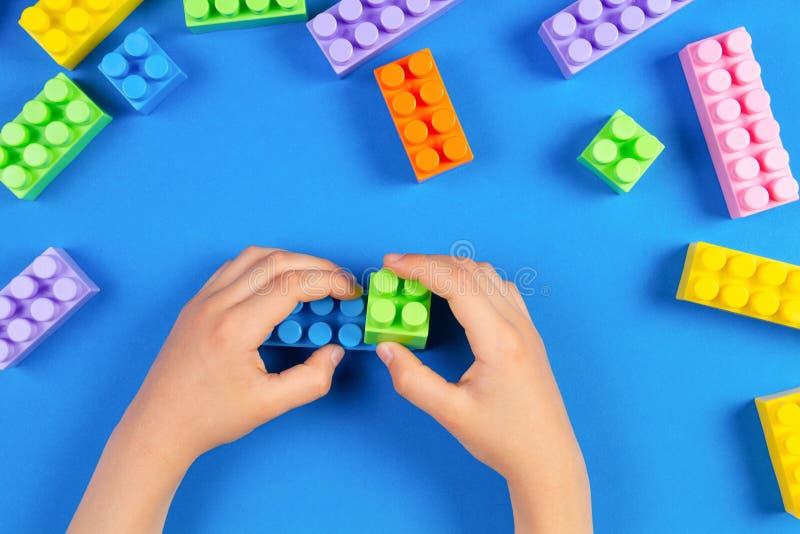 As crianças entregam o jogo com blocos plásticos coloridos da construção no fundo azul fotografia de stock