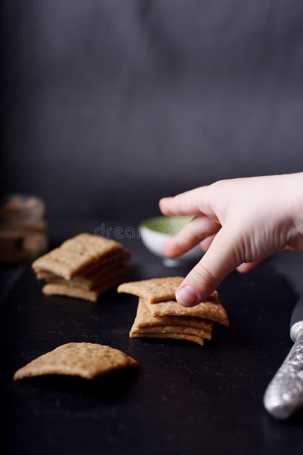 As crianças entregam a tomada de biscoitos inteiros caseiros do trigo no fundo escuro foto de stock royalty free