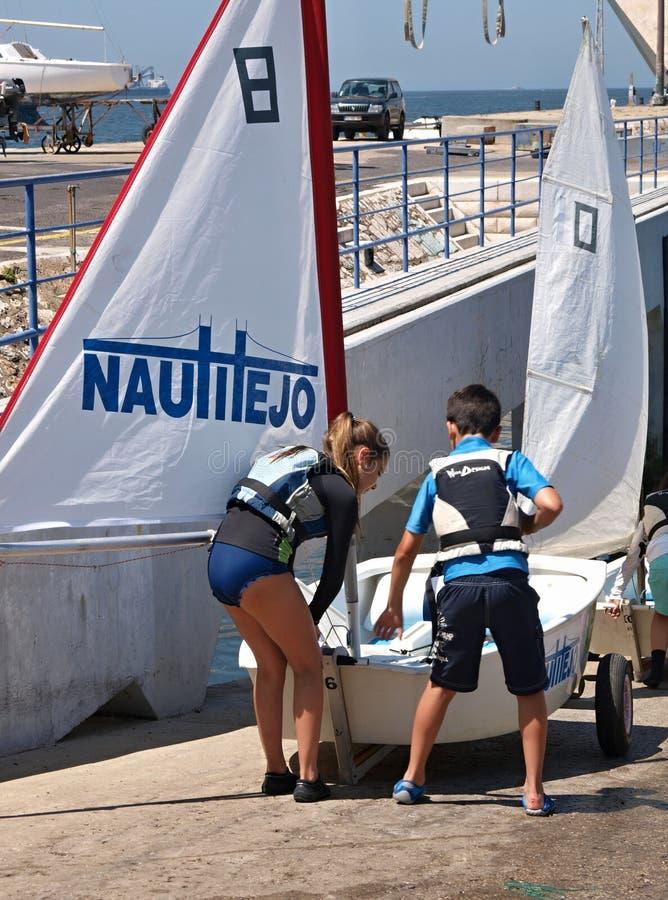 As crianças estão aprendendo a navegar com um pequeno barco foto de stock