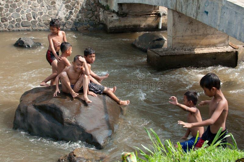 As crianças estão jogando no rio foto de stock