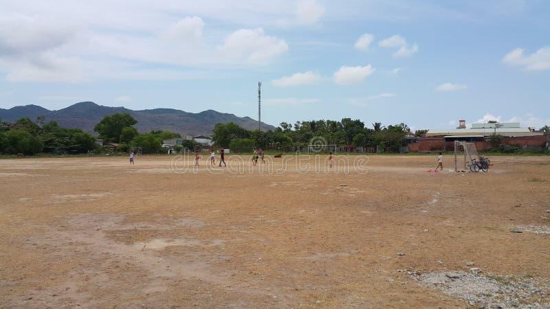 As crianças estão jogando o futebol no campo em Vietname fotos de stock