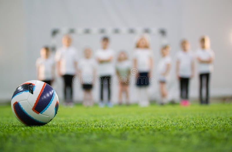 As crianças estão na linha em um campo de futebol Bola do futebol no primeiro plano fotos de stock royalty free