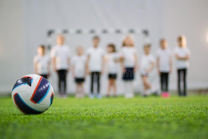 As crianças estão na linha em um campo de futebol Bola do futebol no primeiro plano foto de stock