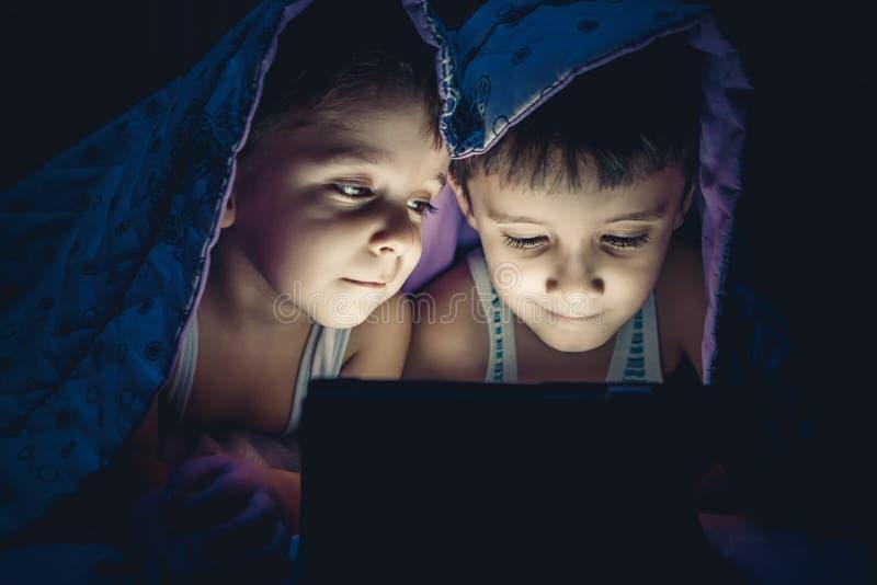 As crianças estão olhando a tabuleta imagem de stock royalty free