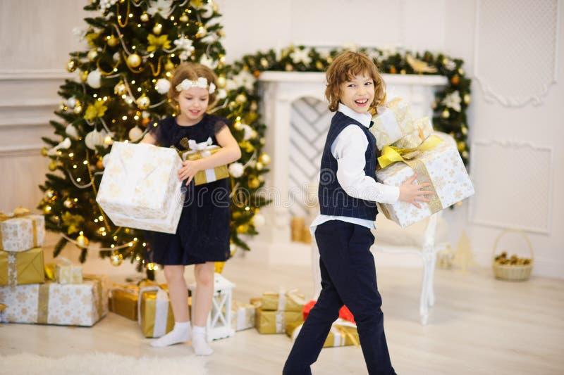 As crianças estão perto da árvore de Natal decorada com as caixas nas mãos foto de stock