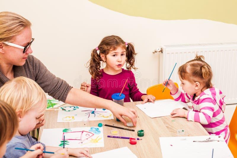 As crianças estão pintando imagem de stock