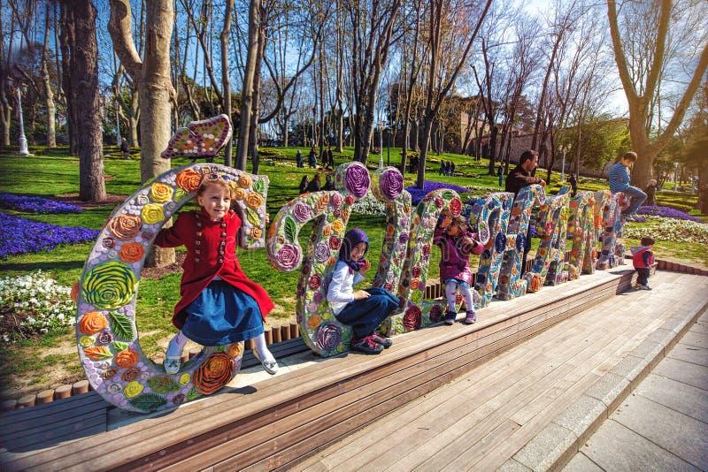 As crianças estão sentando-se no símbolo escultural da flor do parque de Gulhane foto de stock