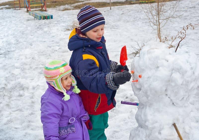 As crianças fazem o boneco de neve fotografia de stock royalty free
