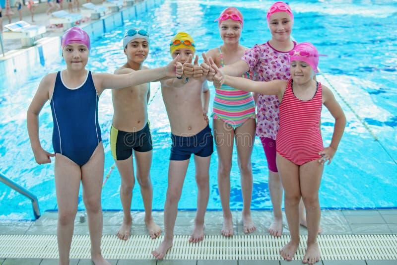As crianças felizes caçoam o grupo na classe da piscina que aprende nadar fotos de stock royalty free