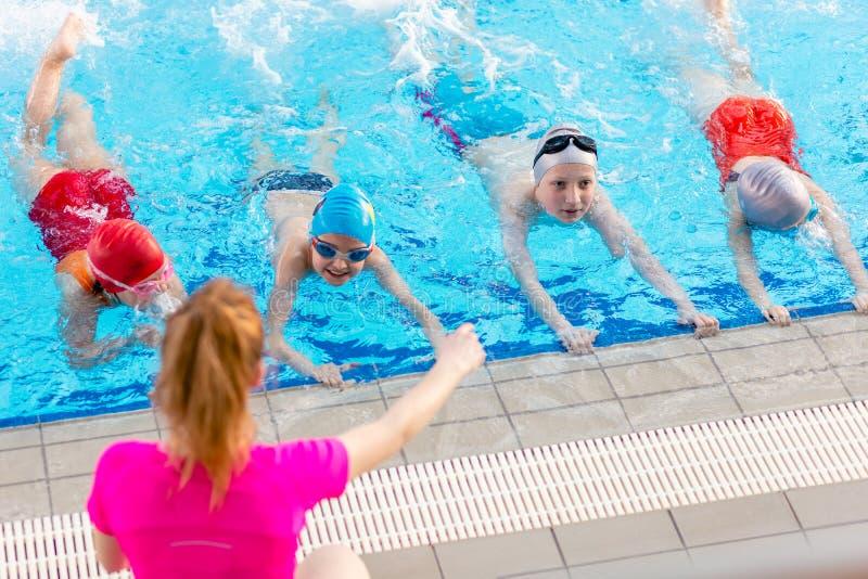 As crianças felizes caçoam o grupo na classe da piscina que aprende nadar imagem de stock royalty free