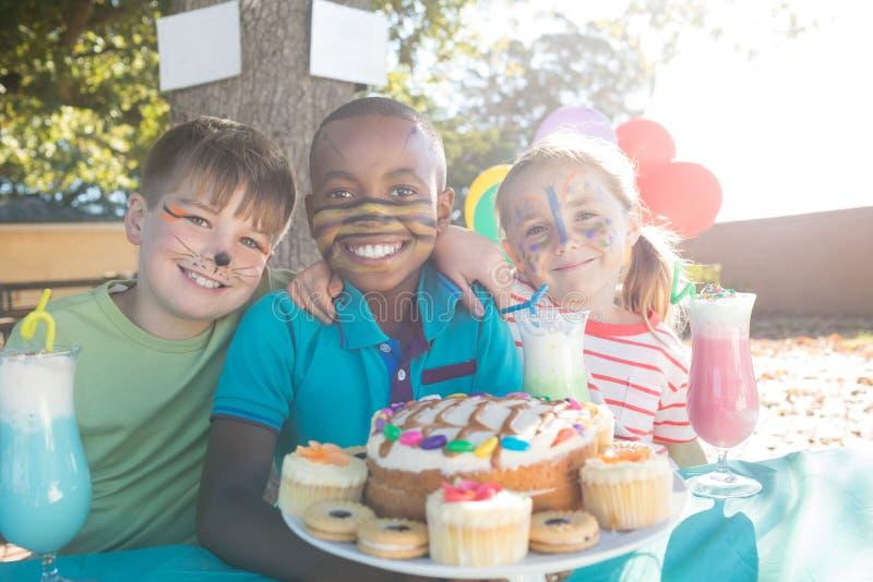 As crianças felizes com cara pintam ter o alimento e as bebidas no parque fotografia de stock