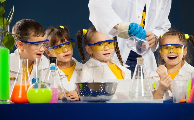 As crianças felizes com o cientista que faz a ciência experimentam no laboratório imagem de stock royalty free
