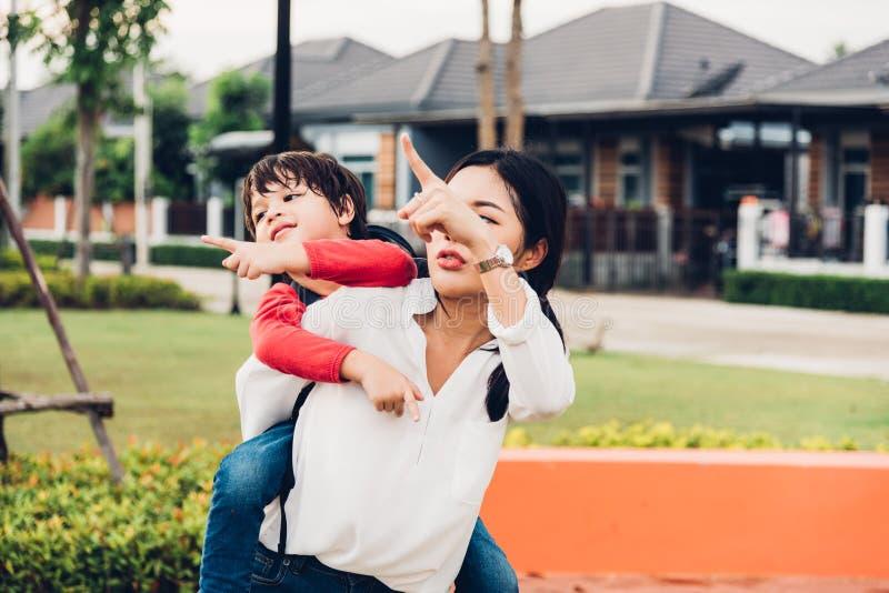 As crianças felizes da família caçoam o jardim de infância do menino do filho que joga a mamã traseira da mãe do reboque do passe foto de stock
