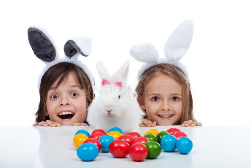 As crianças felizes encontraram o coelhinho da Páscoa e o local de morte dos ovos - isolados no branco fotografia de stock royalty free