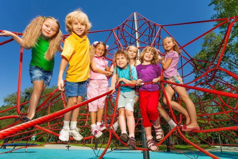 As crianças felizes estão em cordas vermelhas do campo de jogos fotografia de stock