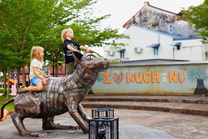 As crianças felizes jogam na estátua engraçada do gato do metal foto de stock royalty free