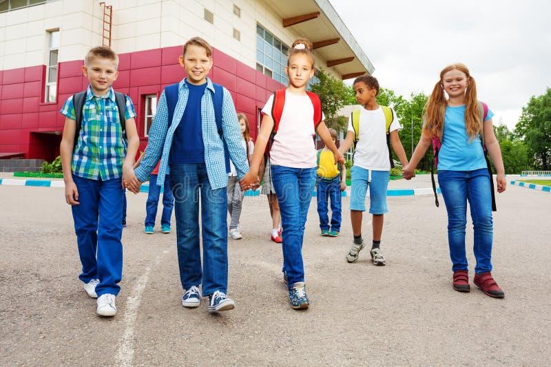 As crianças felizes levam as mochilas, caminhada perto da escola imagem de stock