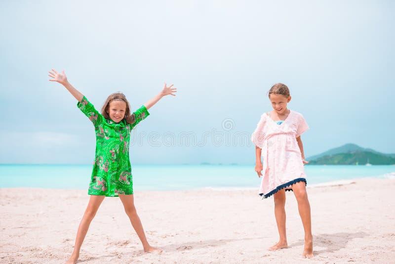 As crianças felizes pequenas têm muito divertimento na praia tropical que joga junto imagens de stock royalty free