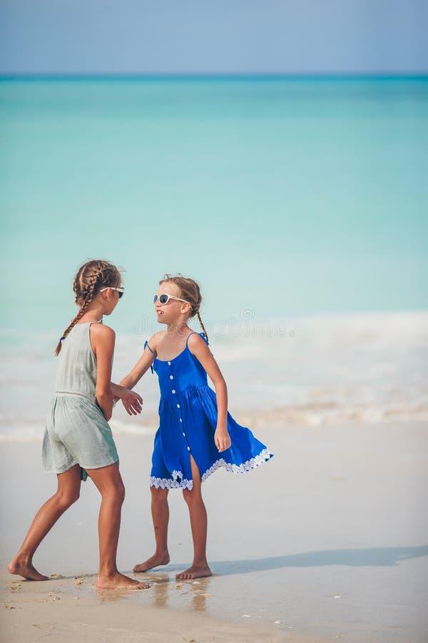 As crianças felizes pequenas têm muito divertimento na praia tropical que joga junto foto de stock