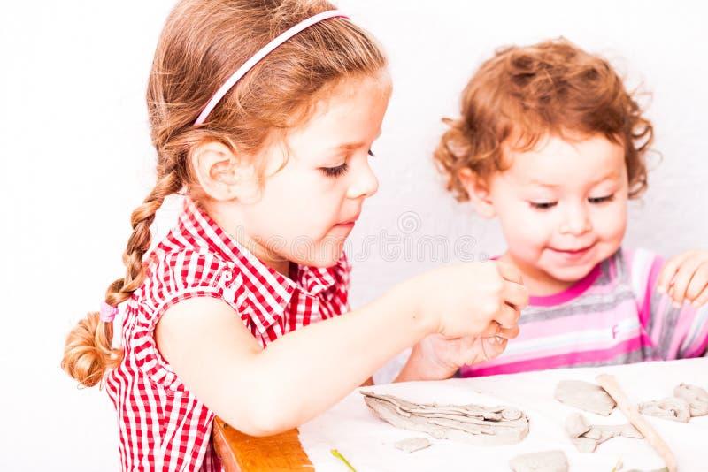 As crianças felizes são contratadas com argila de modelagem fotos de stock