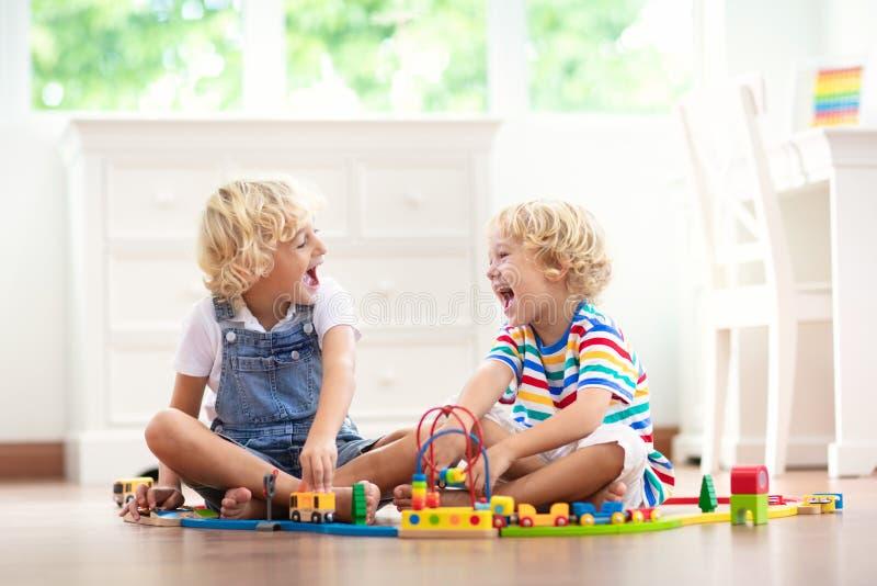 As crianças jogam a estrada de ferro de madeira Crian?a com trem do brinquedo foto de stock