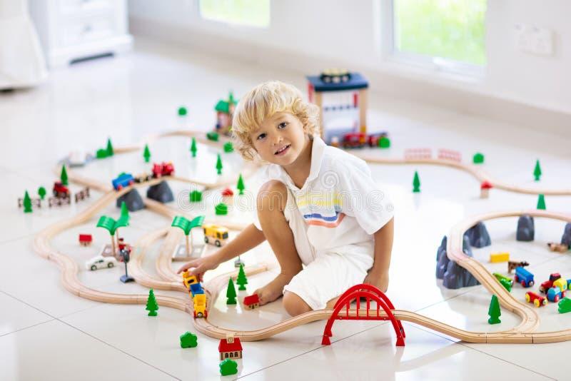 As crianças jogam a estrada de ferro de madeira Crian?a com trem do brinquedo fotos de stock