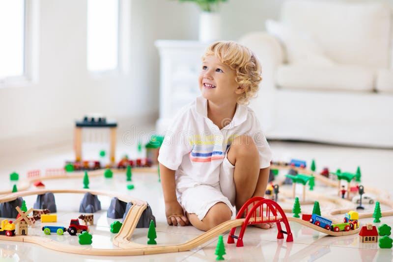 As crianças jogam a estrada de ferro de madeira Crian?a com trem do brinquedo imagem de stock royalty free