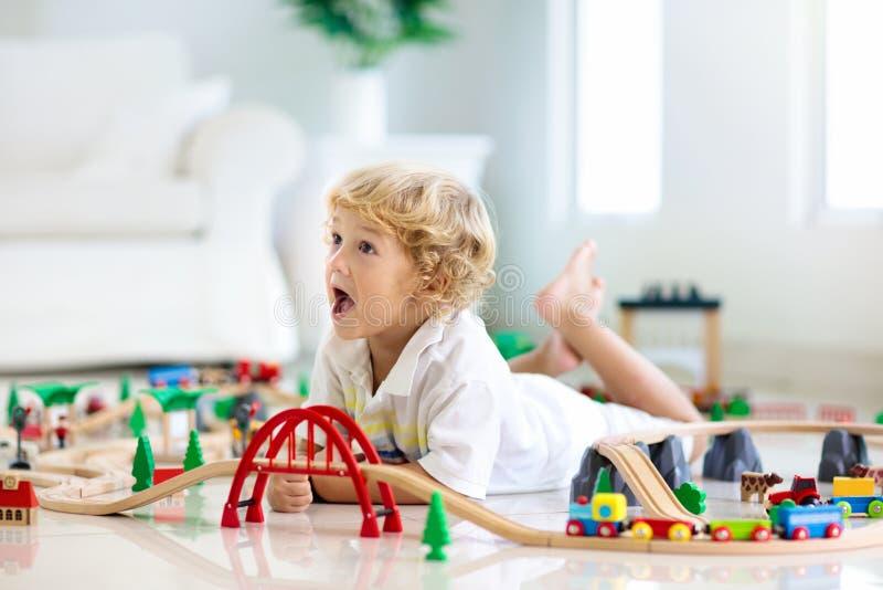 As crianças jogam a estrada de ferro de madeira Crian?a com trem do brinquedo fotografia de stock royalty free