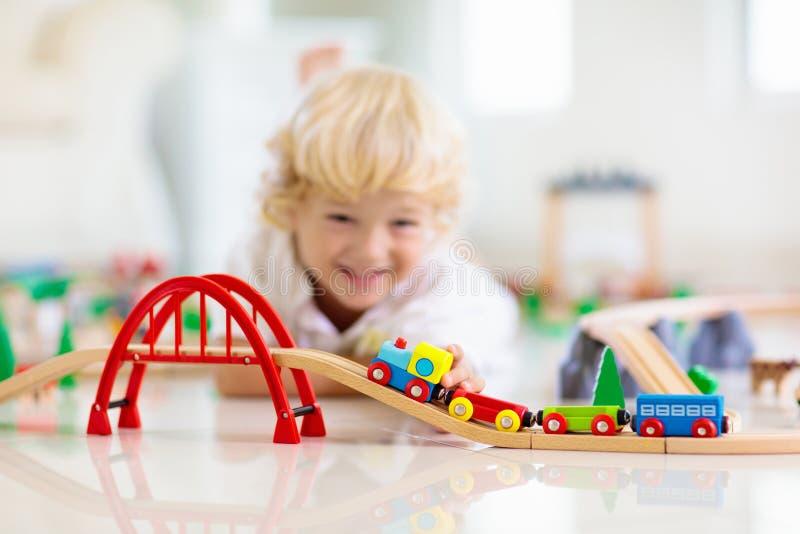 As crianças jogam a estrada de ferro de madeira Crian?a com trem do brinquedo imagens de stock royalty free