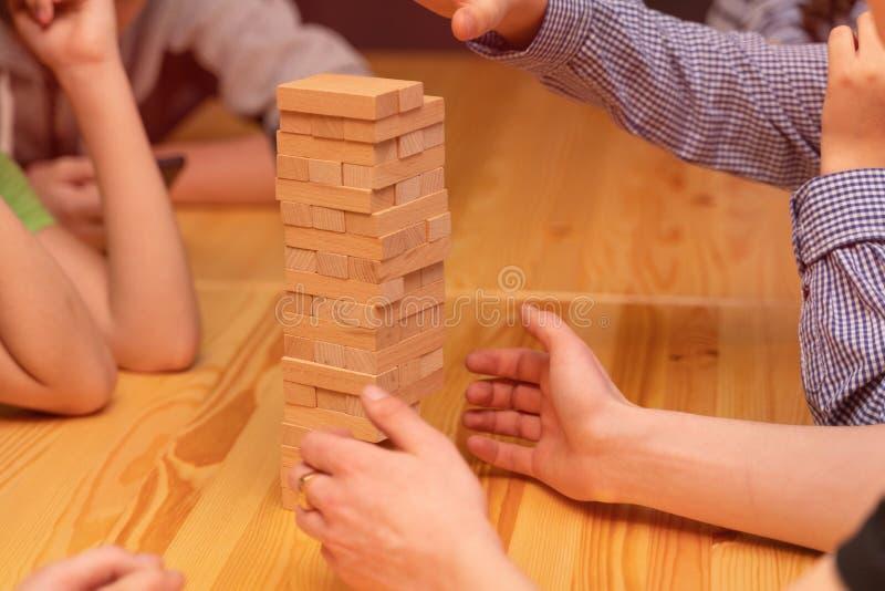 As crianças jogam um jogo de mesa, uma torre de madeira imagens de stock