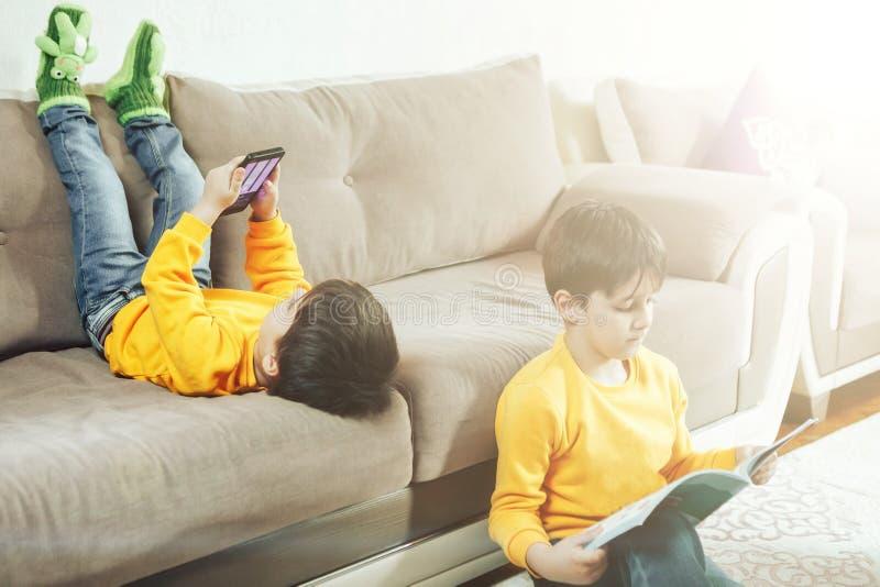 As crianças leem um livro e jogam-no pelo telefone fotos de stock royalty free