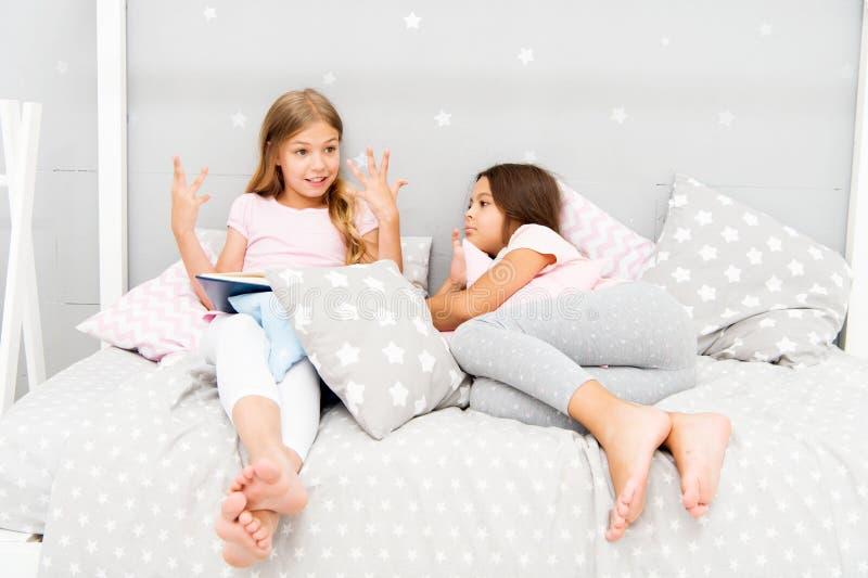 As crianças leram o livro na cama Ler antes da cama pode ajudar a dormir melhor na noite Histórias que cada criança deve ler Famí foto de stock royalty free