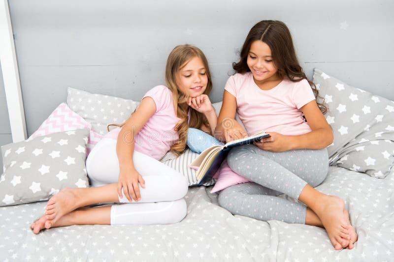 As crianças leram o livro na cama Os melhores amigos das meninas leram o conto de fadas antes do sono Os melhores livros para cri imagem de stock