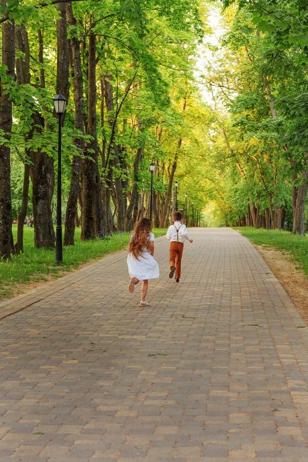 As crianças menino e menina correm ao longo do trajeto no parque fotografia de stock royalty free