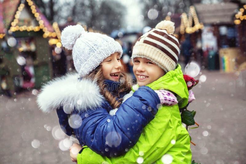 As crianças menino e menina encontraram-se na cidade, abraçando e exultando O conceito do estilo de vida, amor, o dia de Valentim imagens de stock royalty free