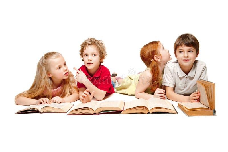 As crianças menino e meninas que colocam com os livros isolados no branco foto de stock