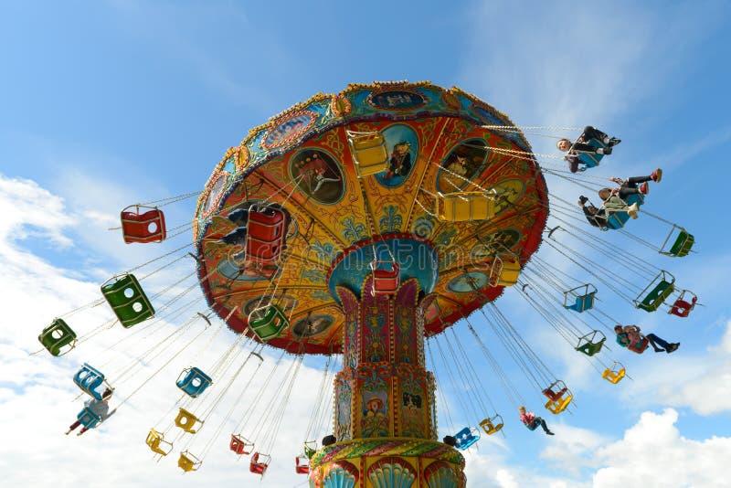 As crianças montam no carrossel em um parque de diversões contra um céu azul Cheboksary R?ssia foto de stock royalty free