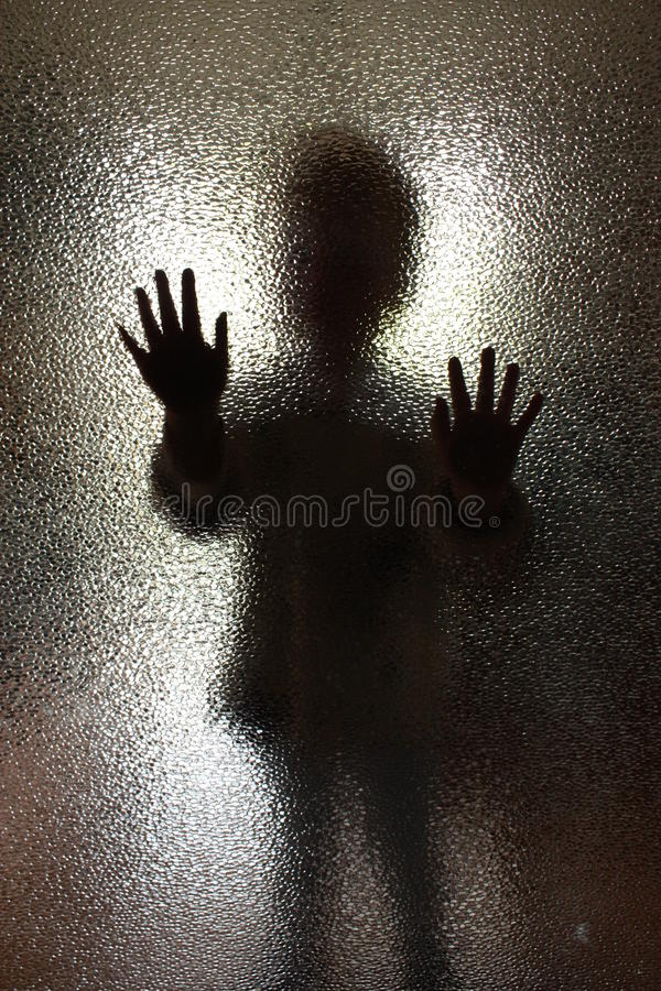 As crianças mostram em silhueta atrás de uma porta de vidro fotografia de stock