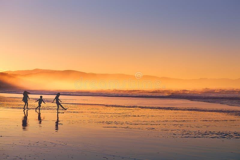 As crianças mostram em silhueta o jogo e ter do divertimento na praia no por do sol imagens de stock royalty free