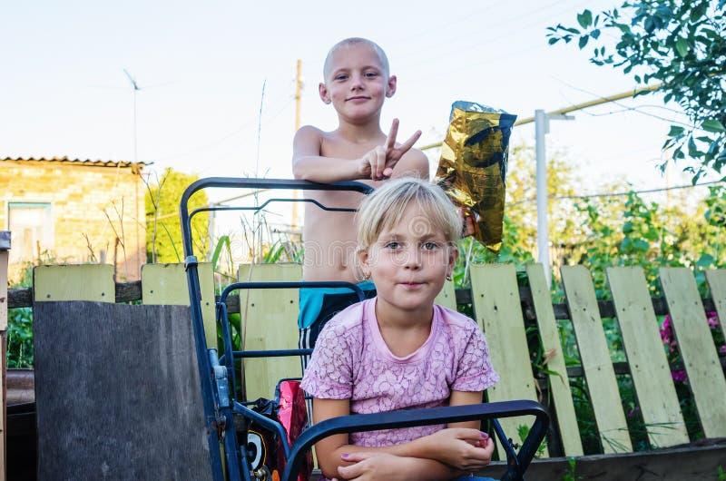 As crianças na jarda da casa rural, irmã do irmão fazem chifres imagens de stock royalty free