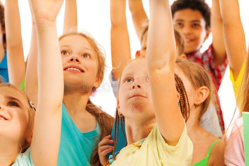 As crianças na multidão sorriem e aumentam as mãos imagens de stock royalty free
