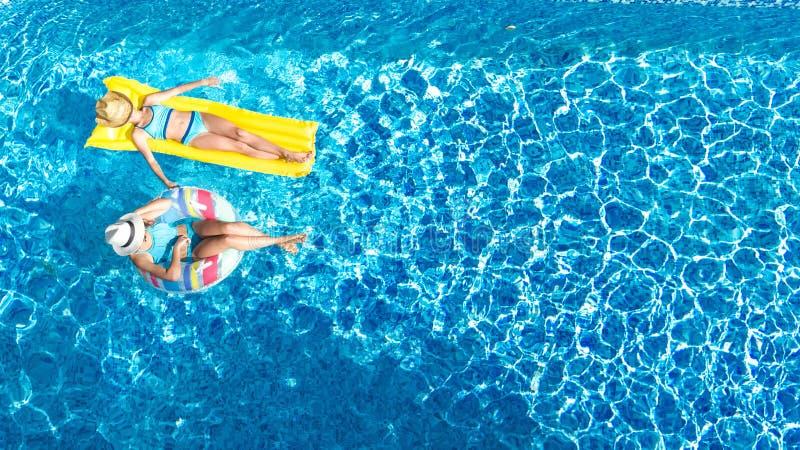 As crianças no fom aéreo da opinião do zangão da piscina acima, crianças felizes nadam na filhós e no colchão infláveis do anel imagem de stock