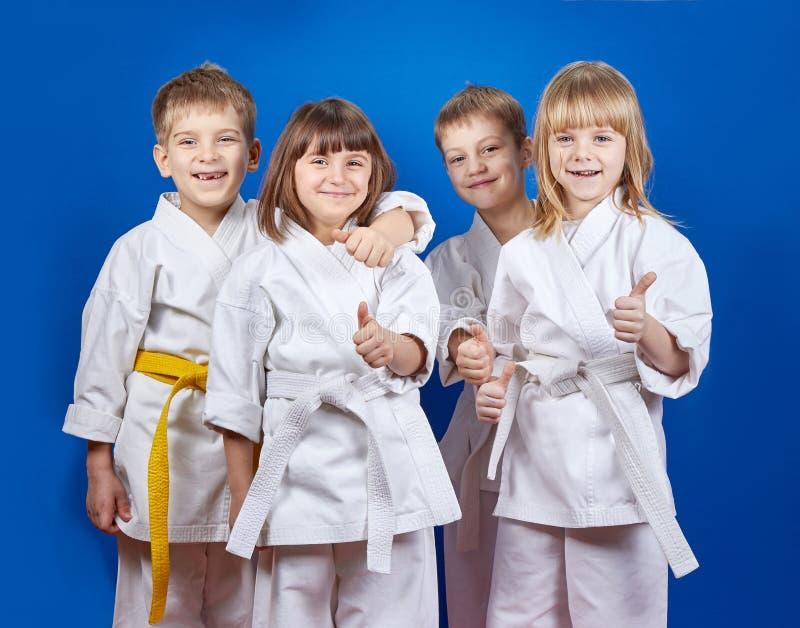 As crianças no karategi estão mostrando o dedo super imagem de stock royalty free