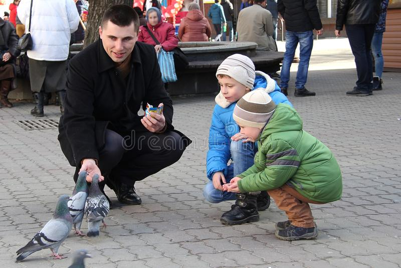 As crianças no quadrado de cidade alimentam os pombos foto de stock