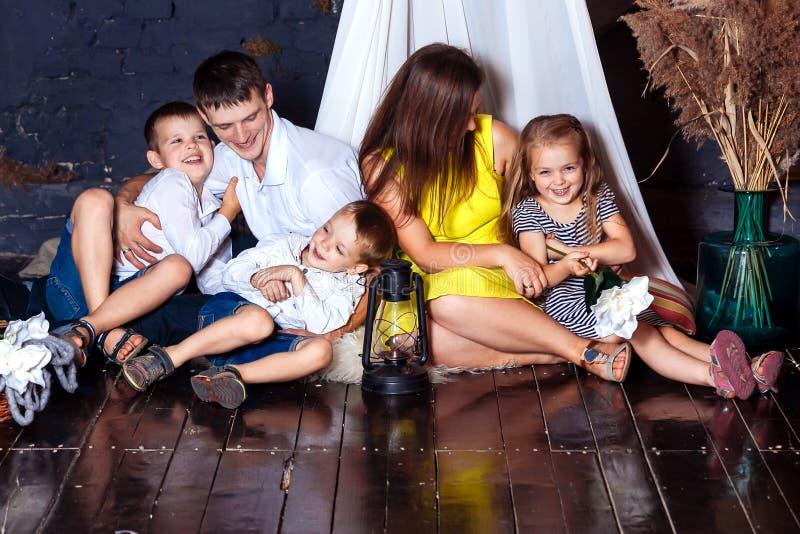 As crianças novas do pai da mãe das crianças da casa do cockloft da família sentam o assoalho de aperto feliz do menino da menina imagens de stock royalty free
