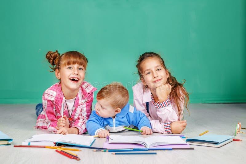 As crianças pequenas escrevem, tiram e leem no assoalho O conceito o imagem de stock