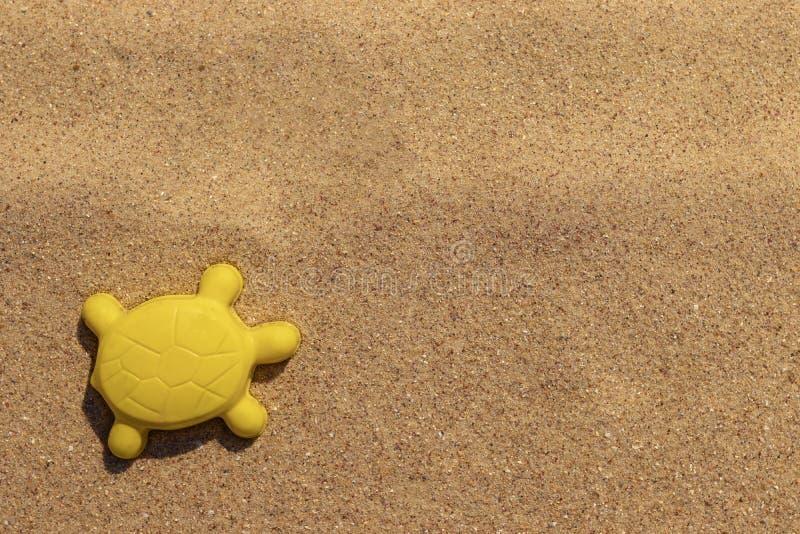 As crian?as pl?sticas amarelas brilhantes brincam na forma da tartaruga na areia Molde animal Conceito da recrea??o da praia para fotografia de stock royalty free