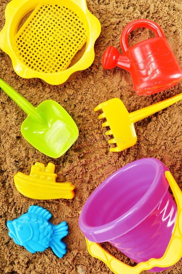 As crianças plásticas brincam jogando no sandpit ou em uma praia fotos de stock