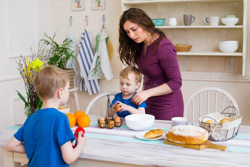 As crianças que ajudam a mãe fazem cookies na cozinha moderna fotografia de stock royalty free